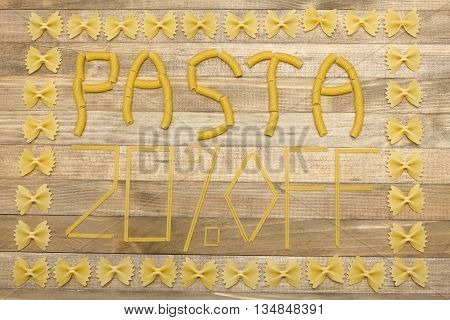 pasta twenty percent off text made of raw pasta on wood