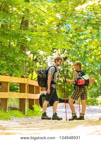 Adventure tourism active lifestyle- young couple backpacker hiking in forest pathway