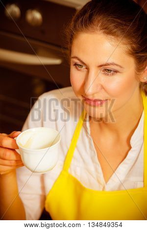 Mature woman in apron holding cup of coffee in kitchen. Housewife female relaxing resting sitting on floor.
