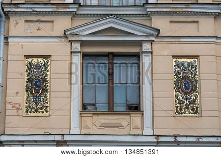 Fragment of classic building wall. Window with a portico and a golden mosaic.