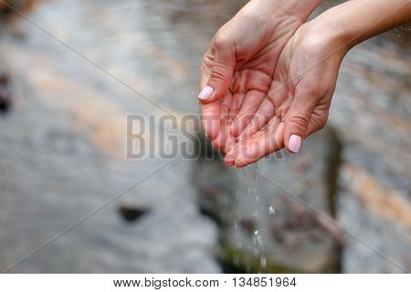 Beautiful female hands scooped water from a pure spring