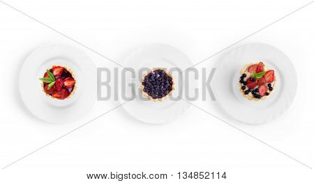 collection of desserts with strawberries and currants on a plate on a white background