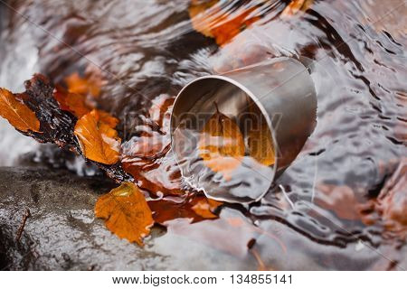 Metal cup lay at a spring of pure water