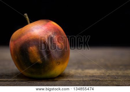Rotten Apple On A Wooden Table