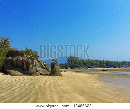 Empty beach paradise in south Goa, rocks on the sand beach, seaside landscape with huge rocks, south India panorama