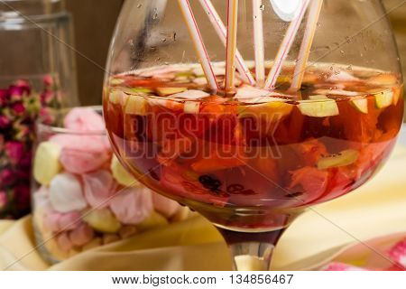 Fruit sugria party big glass, lots of straws on table. Fresh fruits lemonade, cookies, marshmellows, flowers. Happy family celebration.