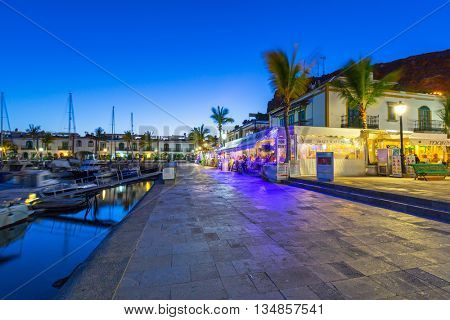 PUERTO DE MOGAN, GRAN CANARIA, SPAIN - APRIL 25, 2016: Pedestrian alley in the harbor area of Puerto de Mogan at night, Gran Canaria in Spain. It's called a Little Venice of the Canaries.
