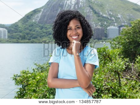 Happy latin woman with curly black hair outdoor on a sea