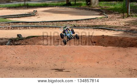 Sydney, Australia - December 14, 2014. Radio controlled buggy car model in race, internal combustion engine on a bumpy red clay road. (St Ives Showground, Sydney, Australia)