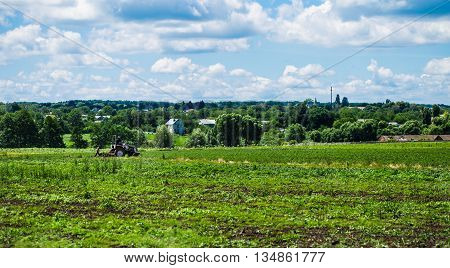 a tractor plows the field in the background of the village and the beautiful sky