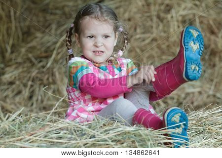 Little braided girl is putting on red gum boots on dried loose grass hay in farm haystack