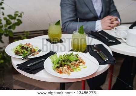 Two plates of fresh salad with arugula, mozzarella, vegetables, tomatoes, chicken served with mint lemonade in a small outdoor restaurant at the lunch with a business man on the background sitting waiting for his meal.