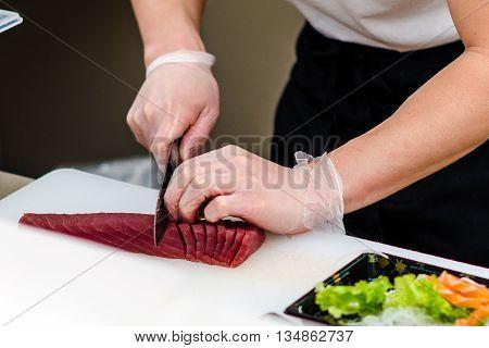 A chef prepair tuna sashimi with knife