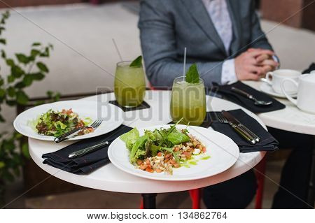Two plates of fresh salad with arugula, mozzarella, vegetables, tomatoes, chicken served with mint lemonade in a small outdoor restaurant at the lunch with a business man on the background sitting and waiting for his meal.