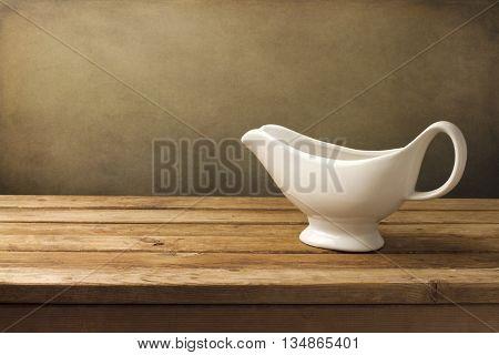 White gravy boat on wooden table over grunge background
