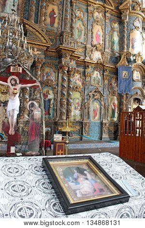 icon lies on the table by beautiful iconostasis with ancient icons set in wooden frame. Religious work of art in the church
