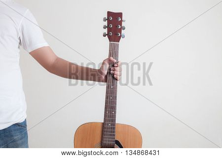 man holding a  guitar and white wall