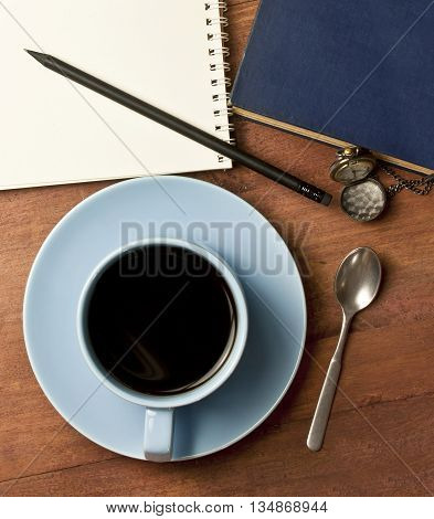 A photo of a desk with a cup of black coffee a notebook a sharp pencil a vintage chain clock and a book shot from above; the concept of a workday or a business person