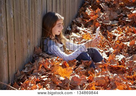 Tween kid girl playing tablet pc in autumn leaves