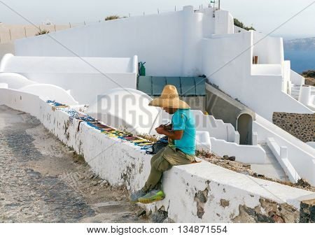 Santorini, Fira - April 30, 2016: Sale of souvenirs on the street in the town of Fira. Santorini is among the top ten most visited tourist destinations in Europe.