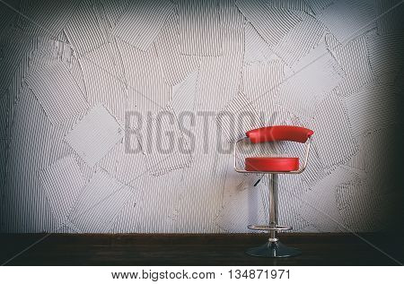 modern red chair in an empty room. in the circle of light there is red swivel chair on a background of gray wall with decorative relief plaster. copy space for your text