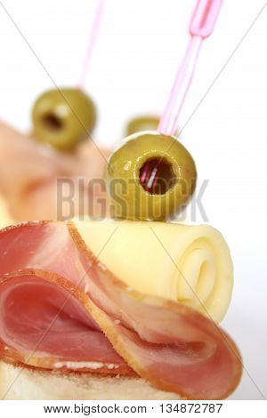 Appetizer with ham, cheese and olives on white background