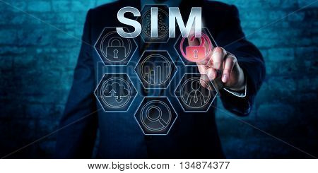 Male cyber security manager is pressing the industry acronym SIM on an interactive touch screen display. Business metaphor and information technology concept for Security information Management.