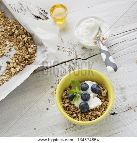 Home crispy golden granola mixture of flakes and nuts on a baking sheet from the oven with yogurt and fresh blueberries. The concept of pure healthy organic food. selective focus