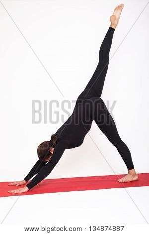 Beautiful athletic girl in a black suit doing yoga. Eka Pada Adho Mukha Svanasana asanas - dogs pose muzzle down with raised leg. Isolated on white background.