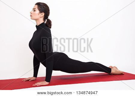 Beautiful athletic girl in a black suit doing yoga. Urdhva Mukha Svanasana asanas - dogs pose muzzle up. Isolated on white background.