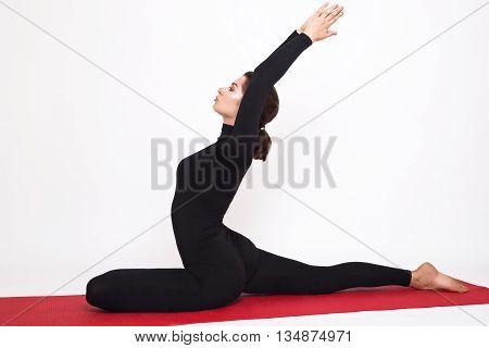 Beautiful athletic girl in a black suit doing yoga. Eka Pada Radzhakapotasana asana - pigeon pose royal. Isolated on white background.
