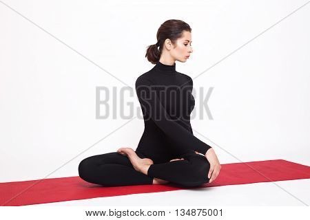Beautiful athletic girl in a black suit doing yoga. Pose of lotus asana Padmasana with housing left unwrapped. Isolated on white background.