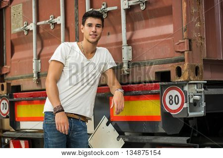 Waist Up Portrait of Young Smiling Man Next to Freight Truck - Unloading Cargo from Container