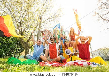 Young football supporter fans cheering with international flags at soccer match - Friends people with multicolored flags having fun - Sport championship concept with warm vivid color tones