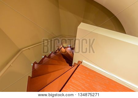 Staircase painted in red. Abstract fragment of the architecture of modern lobby, hallway of the luxury hotel, shopping mall, business center in Lucerne, Switzerland. Interior design.