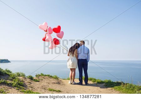 Romantic wedding couple standing on a cliff with red air-balloons