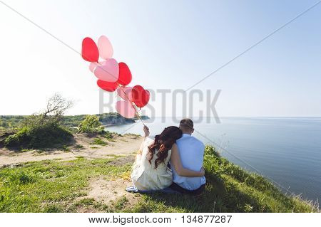 Romantic wedding couple sitting on a cliff with red air-balloons