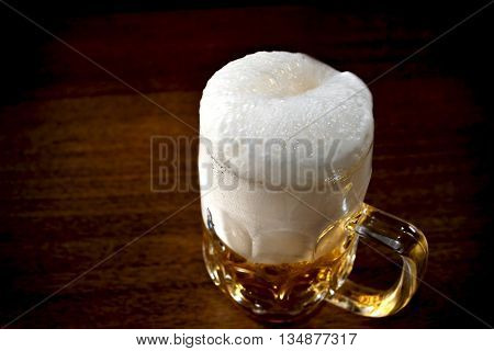 Mug full of beer with froth on the wooden table