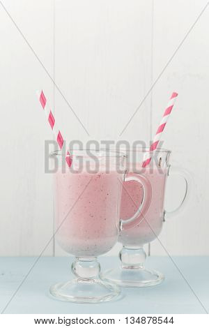 Two milk shakes with strawberries ice-cream pink cocktail with straws on blue wooden table with white background copy space