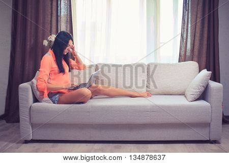 Happy young woman is relaxing on comfortable couch and using laptop at home. Photo toned