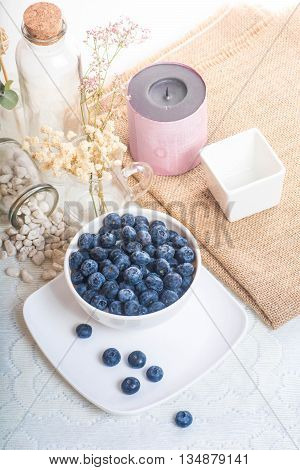 Juicy and fresh blueberries on the table. Bilberry on the white table background. Blueberry antioxidant. Concept for healthy eating and nutrition.