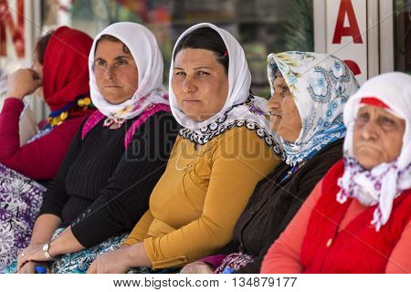 AYDIN, TURKEY - APRIL 4, 2016: Women waiting for their bus to go to their village from the farmers market in the city of Aydin, Turkey.