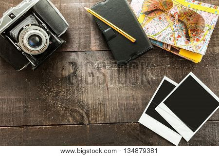 Vintage camera, a map, sunglasses case, polaroid paper a pen and a notebook on a light wood table