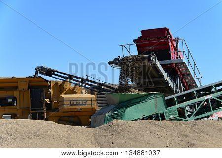 BAKERSFIELD, CA - JUNE 17, 2016: The project for widening State Route 178 is assisted by a temporary rock plant with crusher, conveyors and large piles of aggregate.