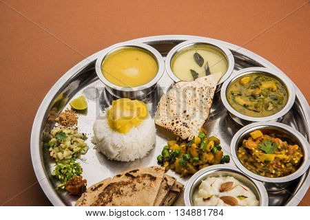 typical maharashtrian food served in a steal plate, marathi food includes kadhi and shrikhand, plain dal, spinach curry, aalu mutter, plain rice, papad, bhakri or bhakar or roti and variety of salad