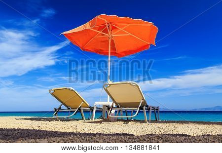 deck chairs and umbrella on background of sea and pebbles
