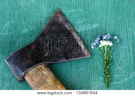 Delicate Bouquet Of Flowers Lying Next To A Rusty Ax. Impersonation Of The Relationship Between Men