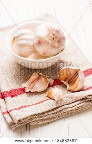 Garlic in white dish on white wooden tabletop