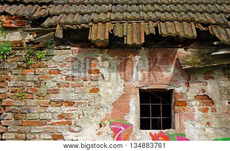 old dilapidated brick house with a grid on the window
