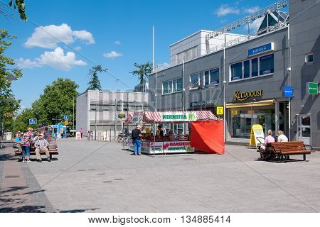 LAPPEENRANTA, FINLAND - JUNE 15, 2016: People sit on the benches and buy strawberry on the Oleksi pedestrian zone - part of the Kauppakatu Street